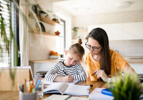 mom hovering over child while she's working