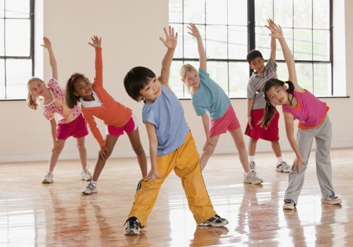 a group of six kids performing dynamic stretches