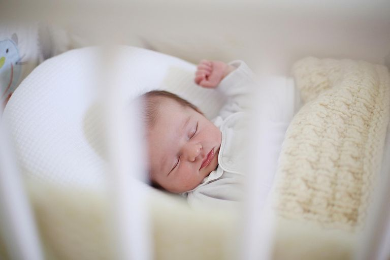 Baby in crib with sleep positioner