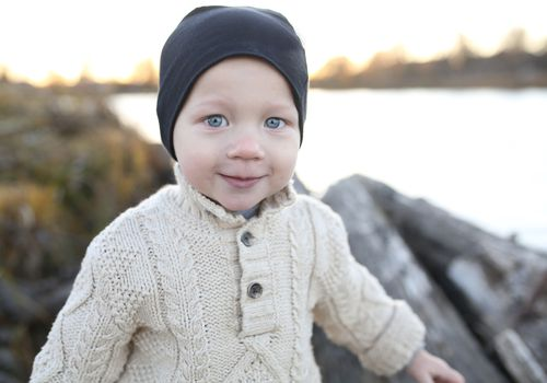 Baby with blue eyes in sweater.
