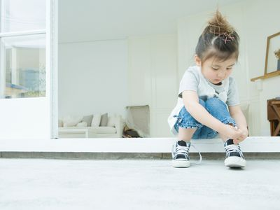 Girl learning to tie her shoelaces