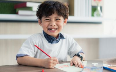 Little boy drawing with colored pencils