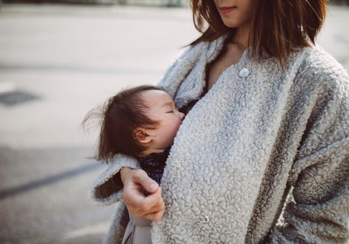Pretty young mom carrying a breastfeeding baby with baby carrier in the street