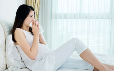 Pregnant person sitting in bed with tissue blowing nose