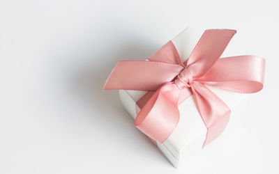 Gift box with pink ribbon on white table