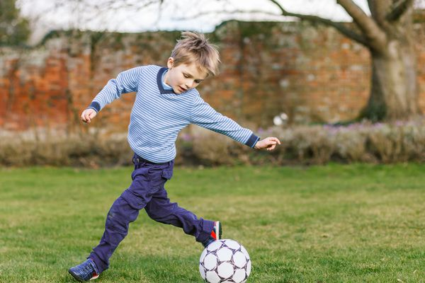 little boy playing with soccer ball