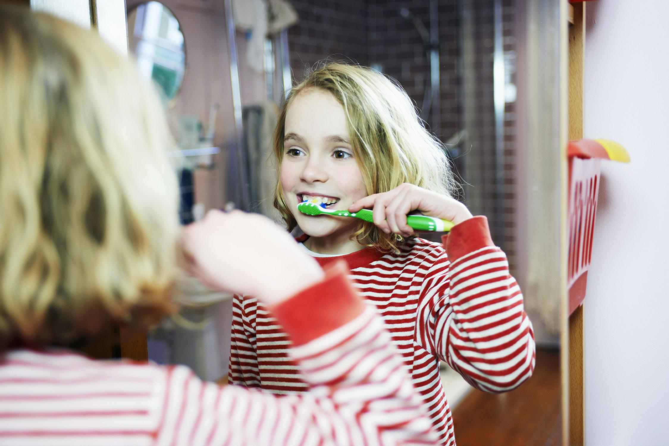 child brushing her teeth in the mirror