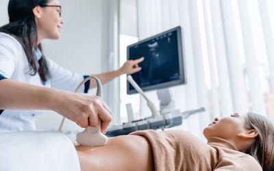 Mid adult female doctor using ultrasound scanner
