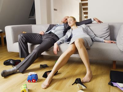 Two parents stretched out and sleeping on a couch
