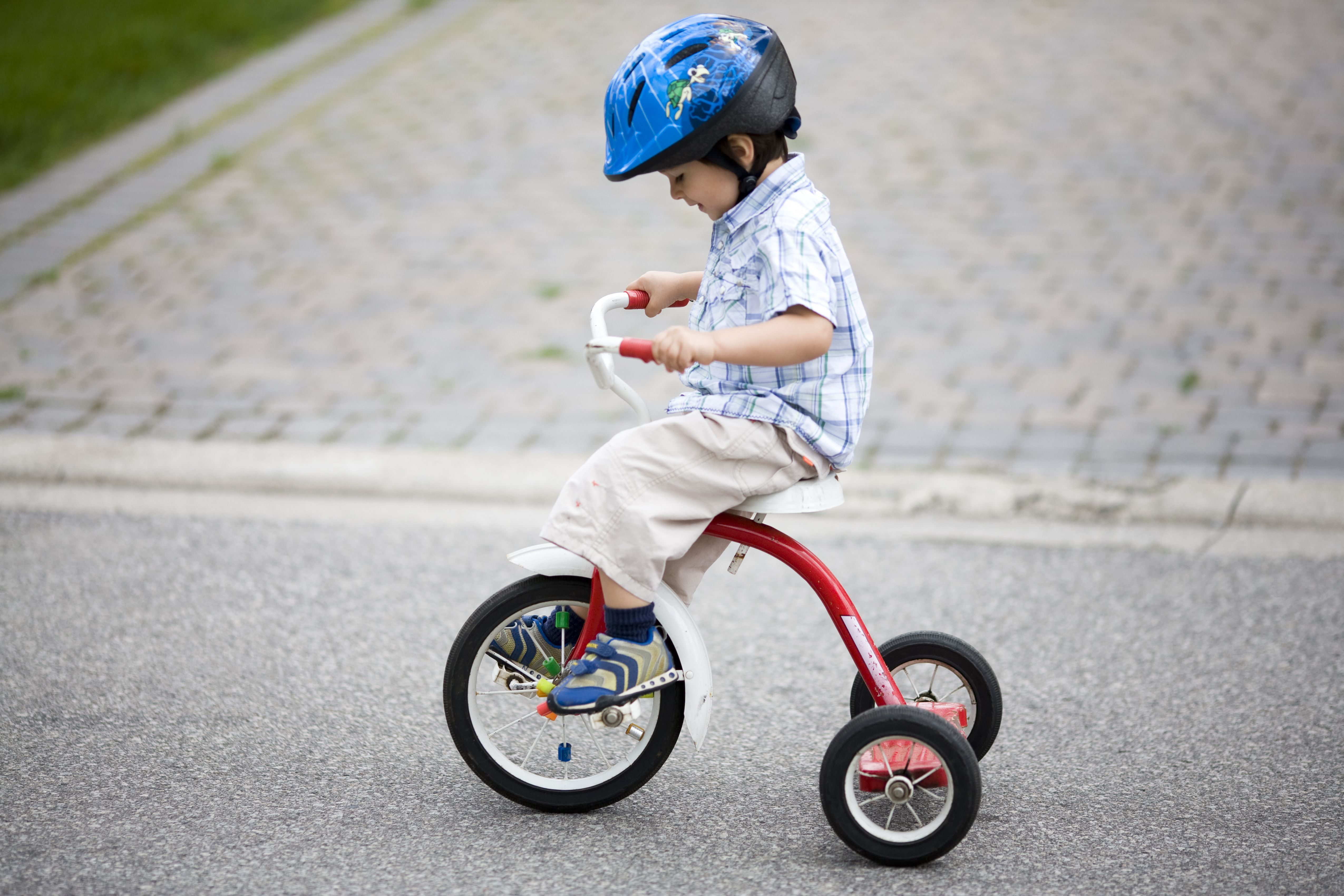 Little boy wearing helmet rides tricycle