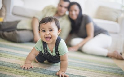 Family with baby boy crawling in living room