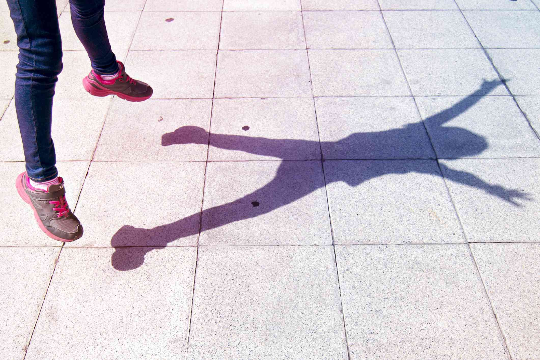 Shadow of a child doing a jumping jack