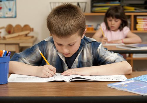 young boy and girl taking test at desks in classroom