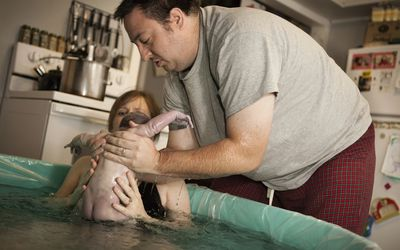 Dad helps catch his baby after a water birth