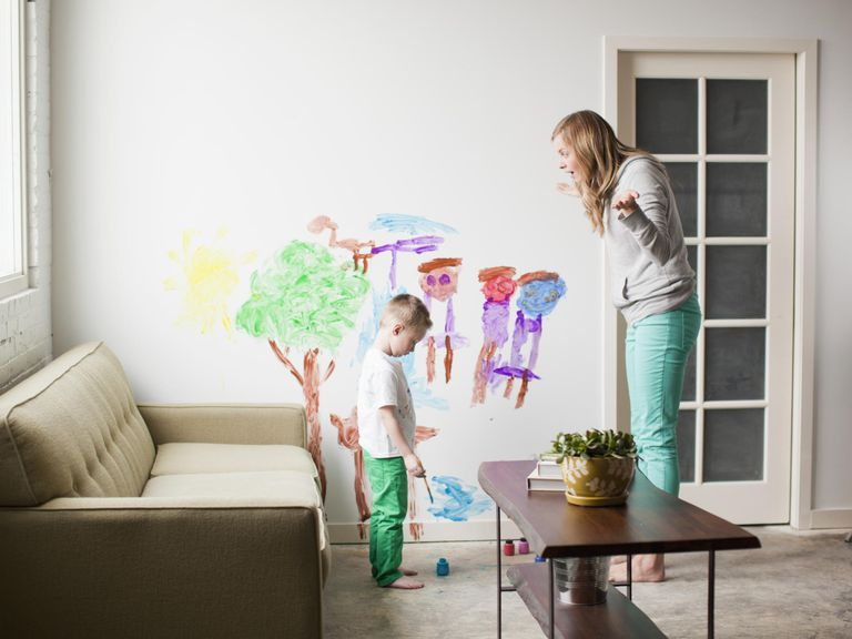 Mother telling toddler boy (2-3) off for painting on walls