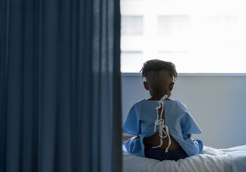 little black boy sitting on a hospital bed