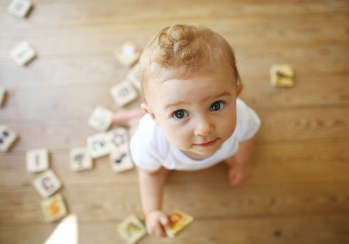 Baby looking up from the floor where he's playing with blocks