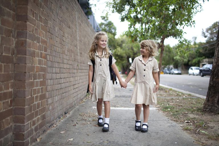 Two young girls walking to school