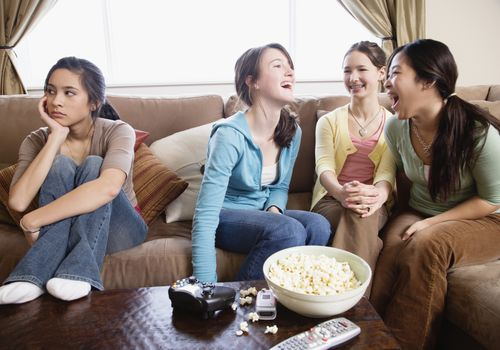 Three tween girls talking and laughing while one looks away