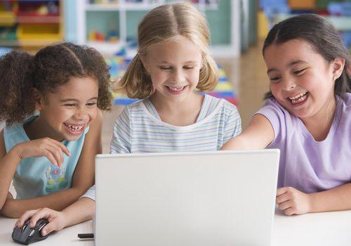 Schoolgirls (4-7) using laptop, smiling