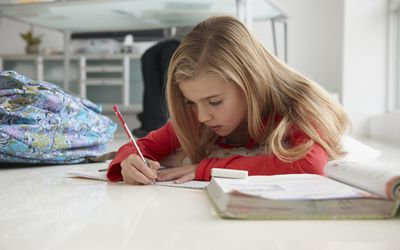 Young girl doing homework on floor of home office.