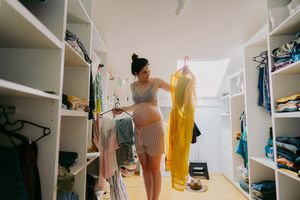 Pregnant women looking through her clothes in the closet