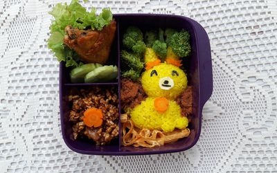 Bento box lunch box for kids featuring a rice bunny rabbit and vegetables.