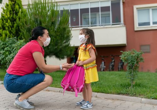 Woman and child wearing masks outside of a school