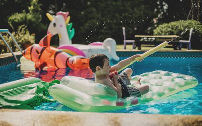 Boy playing with squirt gun in pool