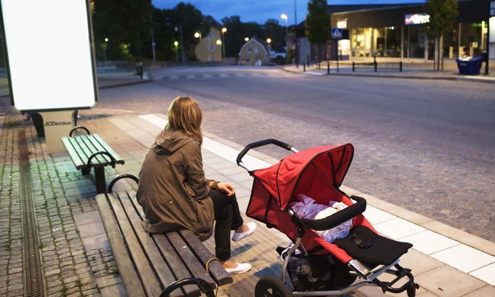 Mom sitting on bench with baby in stroller