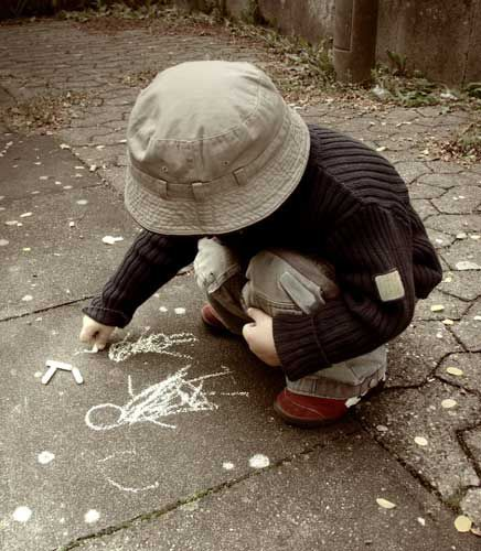 Toddler drawing on sidewalk with chalk