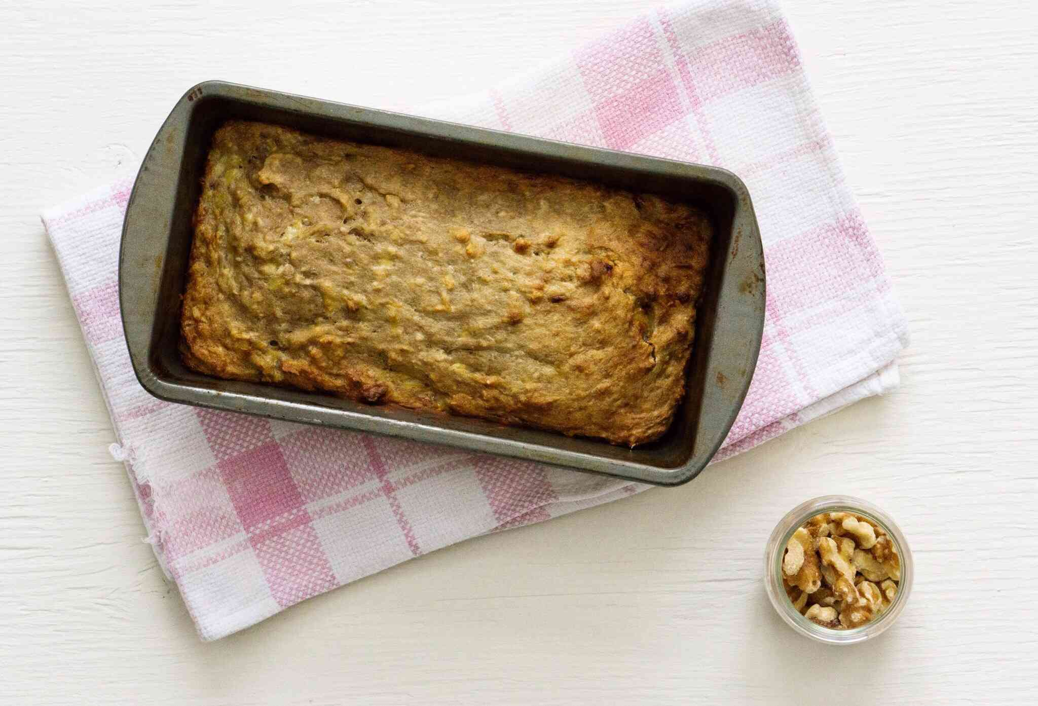 banana bread in pan on pink and white dish towel