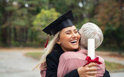 high school graduate hugging mom with diploma