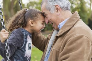 Playful grandfather and granddaughter on swing at playground laughing together