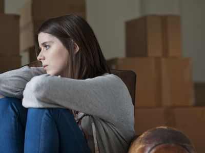 sad teen with moving boxes