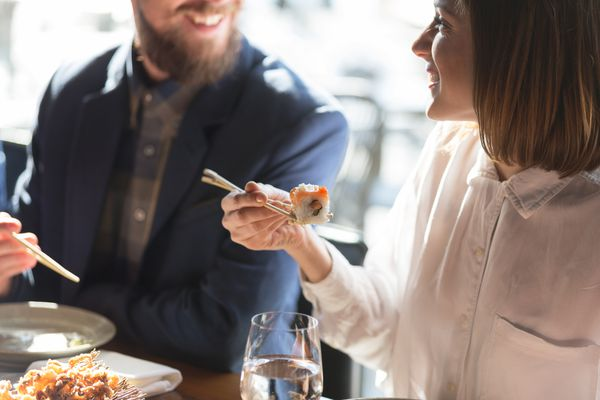 Couple eating sushi and smiling