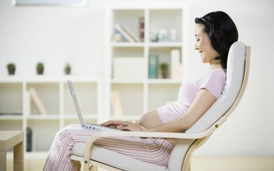 Pregnant woman using laptop, smiling, side view