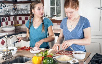 Teens making flatbread pizzas in kitchen