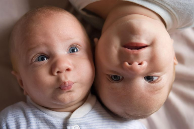 Identical twin baby boys facing opposite directions with their heads together