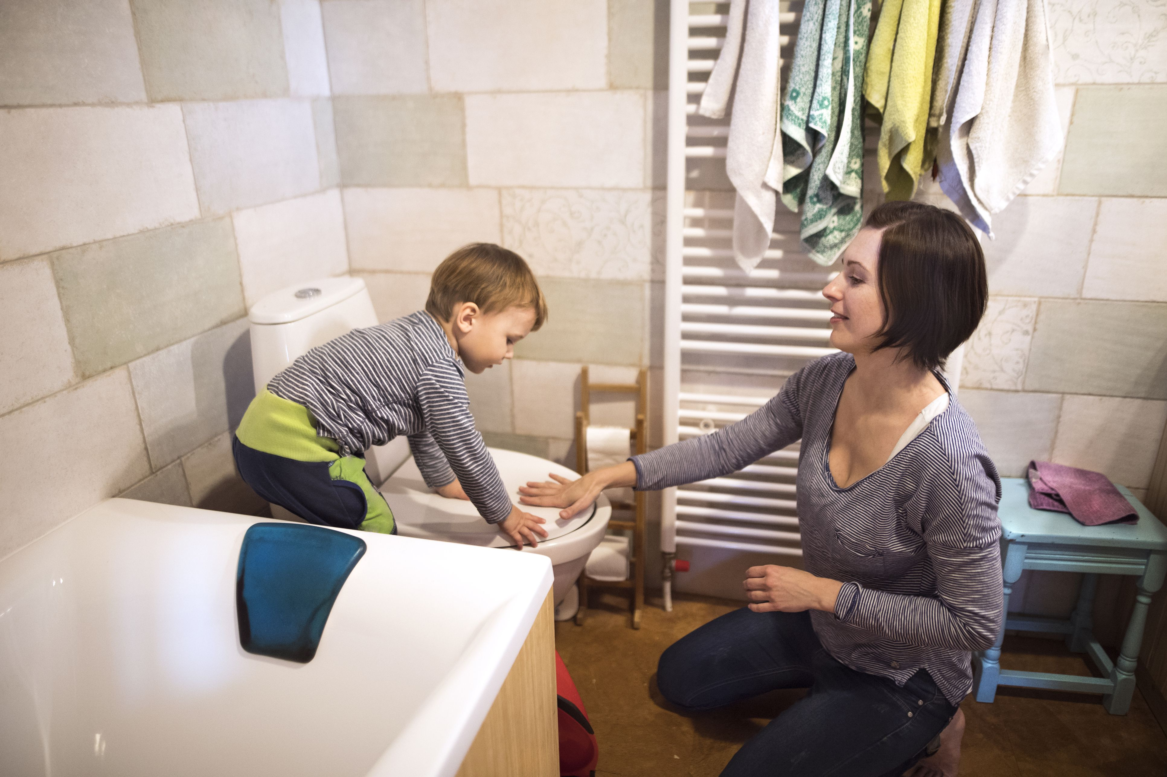 Little boy in bathroom flushing the toilet, beautiful mother helping him