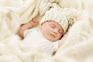 Baby in woven yellow hat sleeping on a fuzzy blanket.