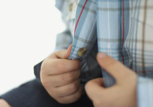 Young boy's hands on an open button-down shirt