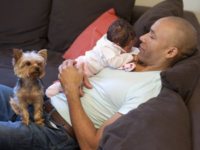 Man holding baby with a dog in his lap
