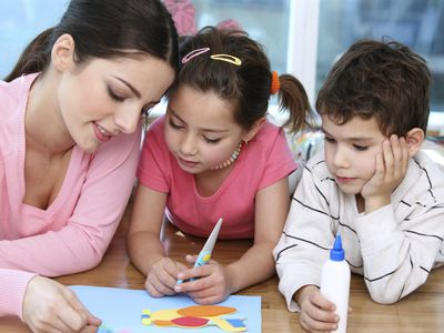Babysitter helping young children with craft