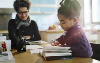 Mother smiles at daughter who is doing homework.