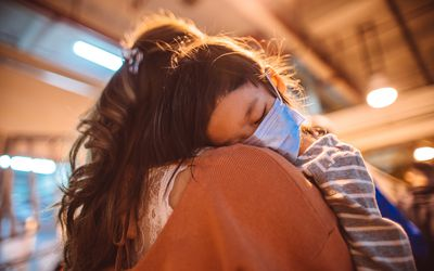 child wearing covid mask sleeping on mother's shoulder