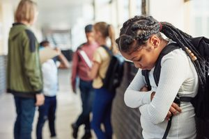 Young girl looking sad while being excluded from her peers in the hallway of a school