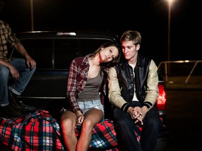 Teen couple sitting in pick up truck bed ay night on playing field