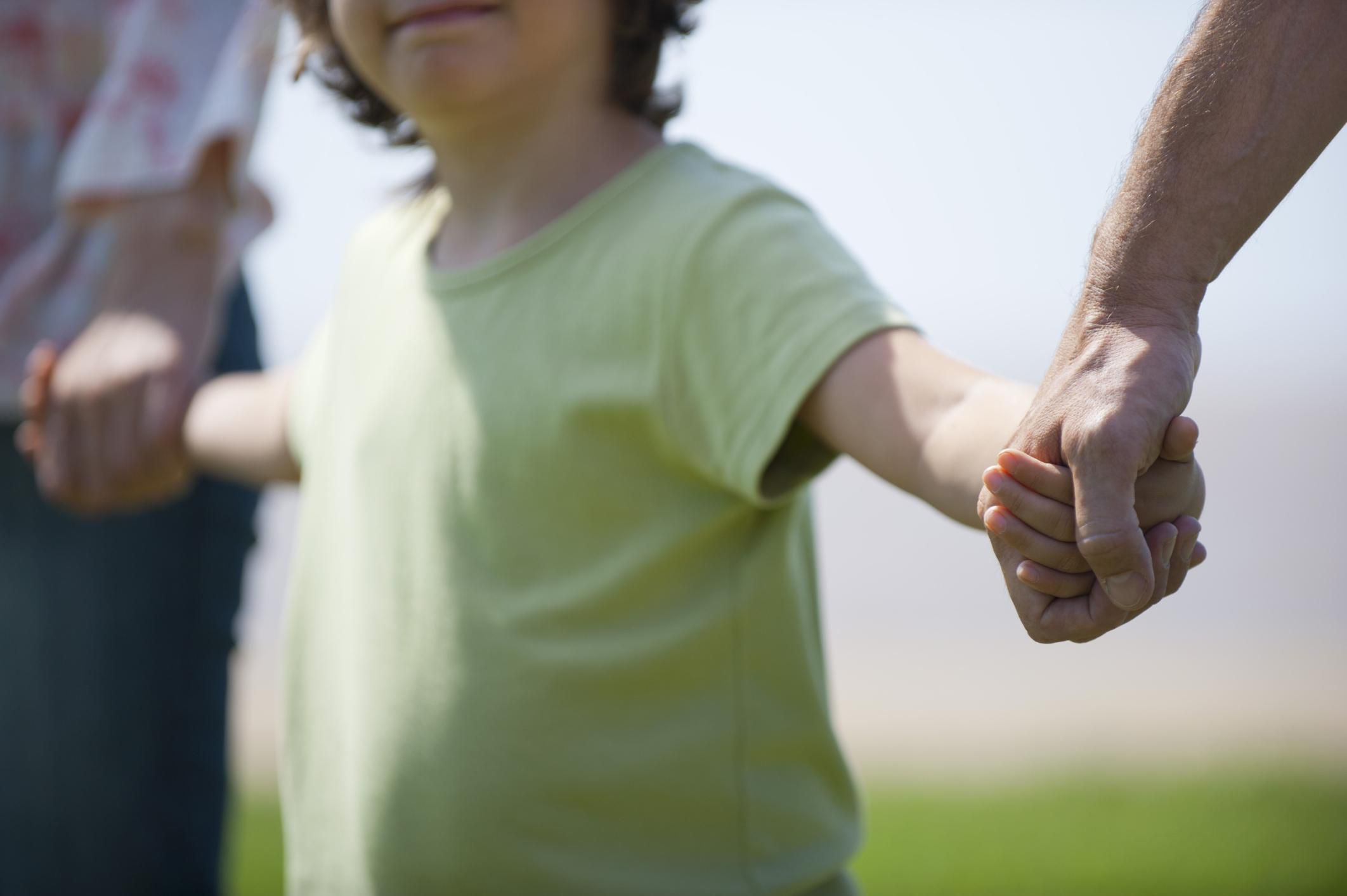 Young child holding man and woman's hands