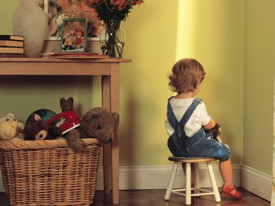 Young child sitting in corner as punishment